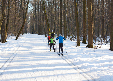 Mom with kids on spring skiing in the forest , view from Zadie
