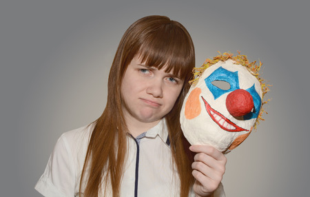 sad girl removes a clown mask  on a gray background