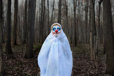 kwade clown in een masker dat zich in een donker bos in een witte sluier