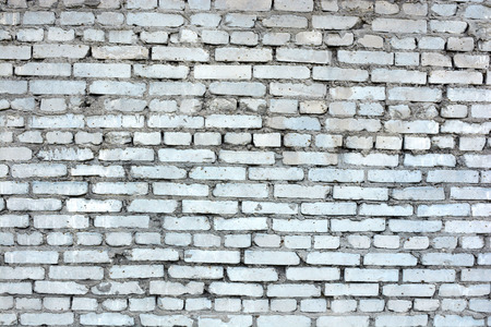 unevenly: background of a white wall and a dirty old brick
