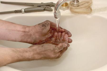 男は配管工として勤務した後汚れた手を洗う
