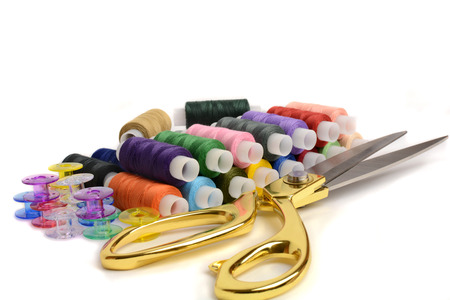 thread for fabric on a white background and scissors