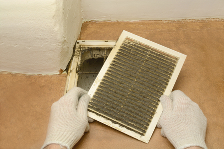 Man removes dust ventilation grilles in white gloves 스톡 콘텐츠