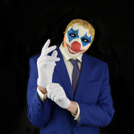 white gloves: Evil clown on black background, man in a clown mask, dressed in a business suit, wear white gloves Stock Photo