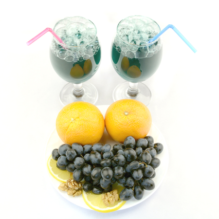 green cocktail poured into two glasses on a white background with fruit