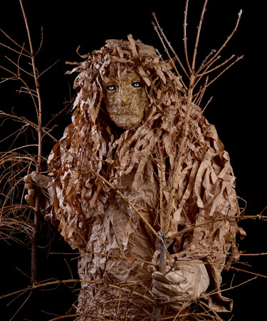 Man in a wood goblin costume, holding a withered trees. Environmental protection