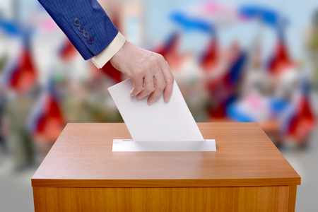 Election Day. Man votes by throwing a ballot in the ballot box