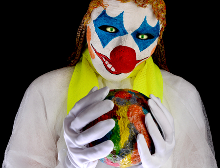 Clown wearing a mask and wearing white clothes is holding a ball in his hand