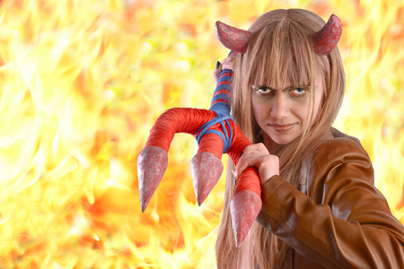 guise: Girl in the guise of a devil with a trident on the background of fire