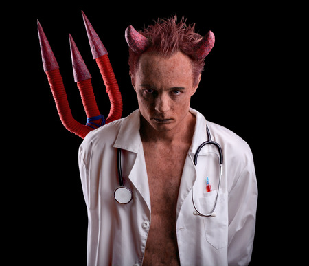 Doctor in the guise of a devil with a trident over his back. Deception in medicine. Stock Photo