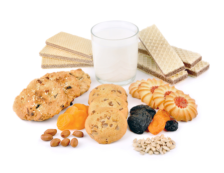 Wafers and oatmeal cookies on a white background. Sweet confectionery products and a glass of milk.