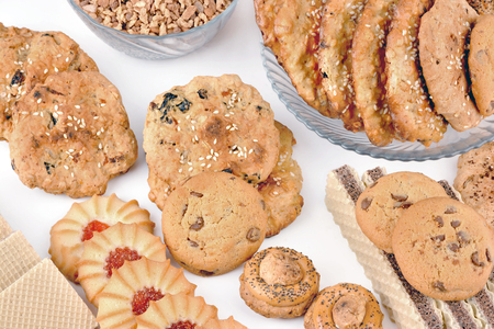 Sweet oatmeal cookies in a plate and waffles on a white table. Various confectionery products.