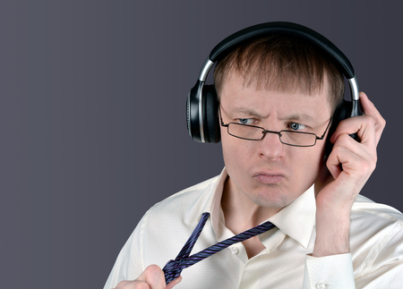 Man indignantly listens to music through headphones. Discontent emotion of a music lover