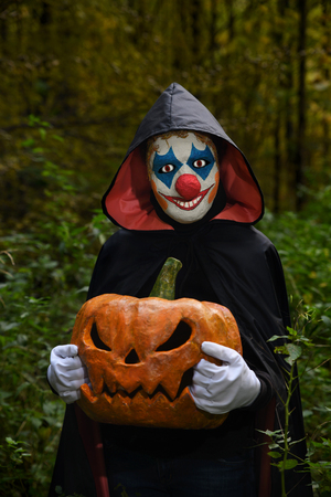 Scary clown in the forest with a pumpkin in hand. Costume clown for Halloween.