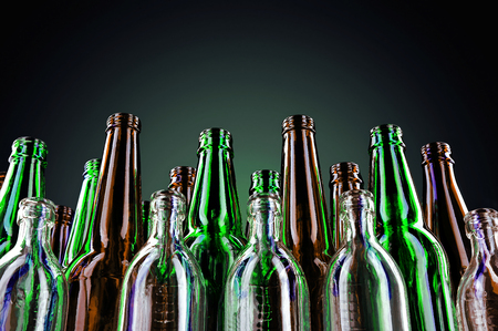 Empty and clean glass bottles on a dark background. Glass containers for various drinks Stock Photo