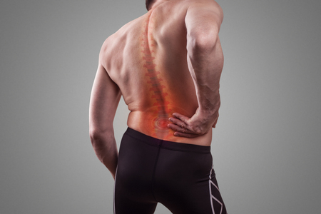 Damage to the lumbar back. A man holds his back in pain. Concept of human injury 版權商用圖片