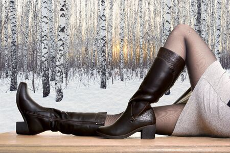 Women's seasonal shoes. Girl shows high boots on a background of a winter birch forest. Concept for winter shoes Foto de archivo