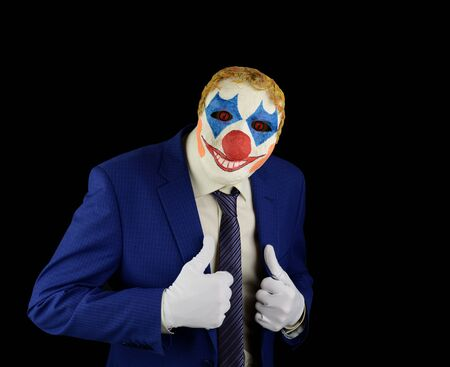 Businessman in a clown mask scares on a black background. Scary business image for Halloween. 免版税图像