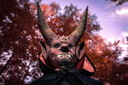 Devil with horns and in a black cloak on a red background. Man in scary mask for Halloween.
