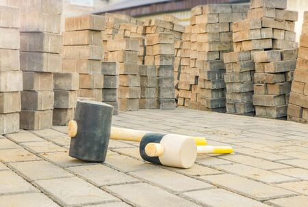 Laying gray concrete paving slabs on leveled yellow sand.  Preparatory work for laying concrete bricks. Rubber hammers Stock Photo