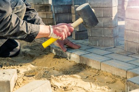 Worker lays the gray concrete paving slabs on the leveled yellow sand, tapping with a rubber mallet. Concrete brick laying technology