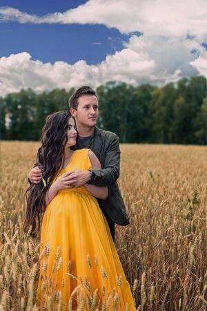 La muchacha embarazada y el novio están parados en un campo de trigo al atardecer. Cultivo de cereales en la agricultura. Jóvenes enamorados Foto de archivo