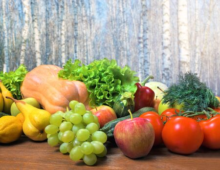 Fresh crop of fruits and vegetables on a wooden table. Products on a background of birch forest. Vegetarian food. The concept of lack of vitamins in the winter.