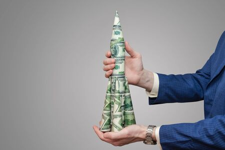 Man in a business suit holds a rocket of paper dollars on an isolated gray background. American currency growth concept Banque d'images