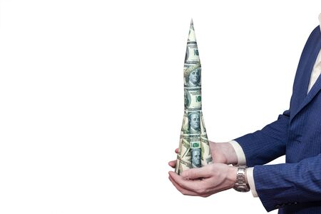 Dollar rocket in the hands of a man on an isolated white background. Concept of growth of the American currency. Фото со стока