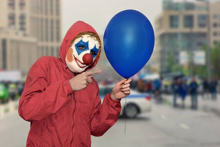 Person in a clown mask scares on the street with a balloon and a needle. Festive fun. Malice concept
