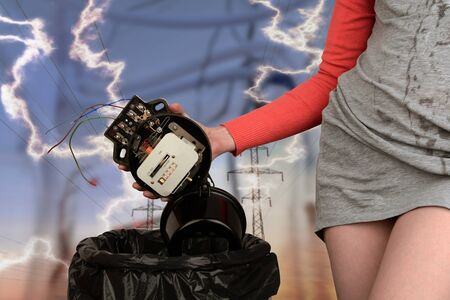 Girl throws an old electric meter into the bin. Concept Replacing a device with a new one