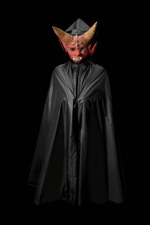 Devil in a cloak on a black background. Man in a scary mask with horns. Halloween holiday