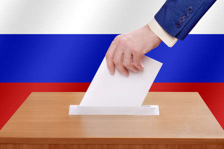 Election day in the Russian Federation. A man votes by throwing a ballot into the ballot box. Stock fotó