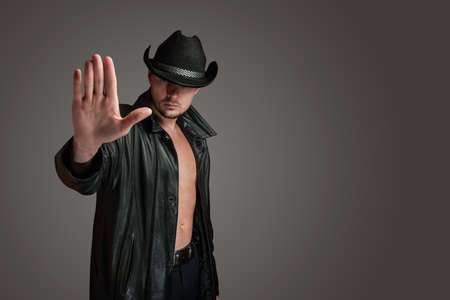 Cowboy in a leather coat makes a gesture of denial with his hand. Unshaven serious man in hat isolated on gray background. Failure concept. Stop gesture. Culture of western america