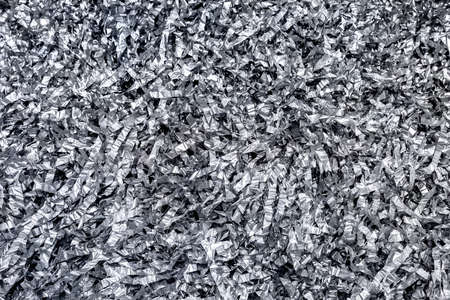 Festive shiny silver tinsel background. The texture of sliced crumpled foil.
