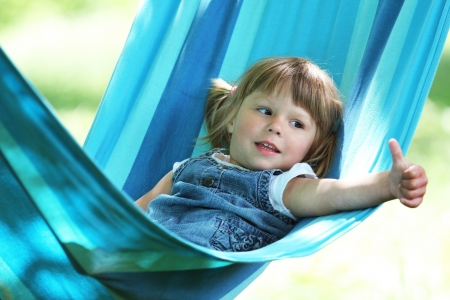a little girl lying on a hammock photo