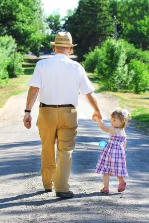grandparents: grandfather and granddaughter are on the road Stock Photo