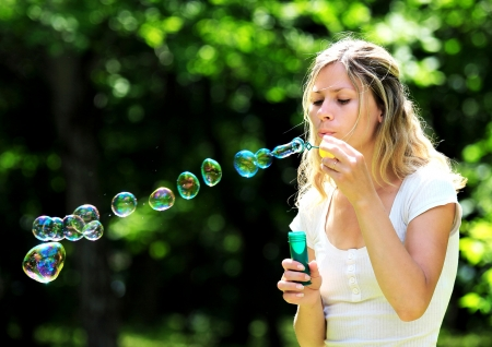 young woman blowing bubbles outdoors photo
