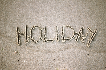 the word  holiday  in the sand on the beach photo