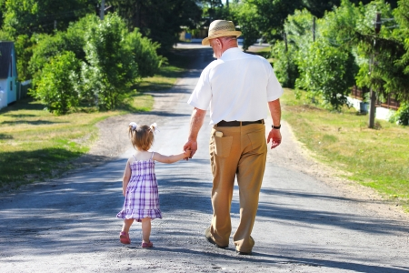 generation: grandfather and granddaughter are on the road Stock Photo