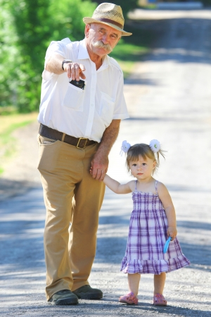 the grandfather: grandfather and granddaughter are on the road Stock Photo