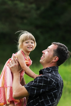 Beautiful little girl with her father on the nature Stock Photo - 14381636