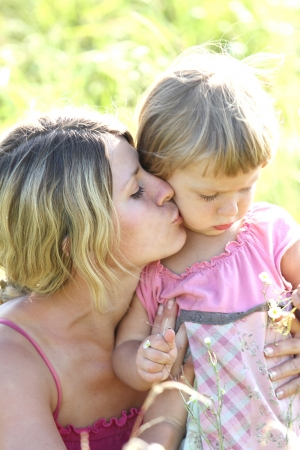 Beautiful little girl with her mother on the nature Stock Photo - 14490421