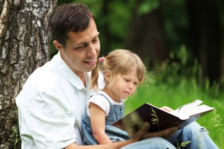 kids writing: father and daughter reads the Bible
