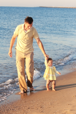 father with a small daughter at the sea shore photo
