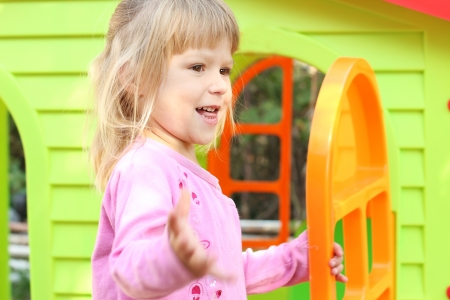 Beautiful little girl with a childrens playhouse Stock Photo