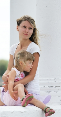 beautiful little girl with her mother outdoors photo