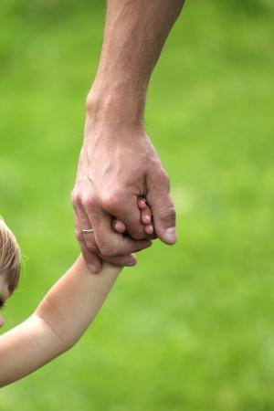 papa y mama: mano de padre e hijo en la naturaleza Foto de archivo