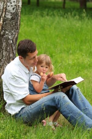 familia en la iglesia: joven padre con hija la lectura de la Biblia Foto de archivo