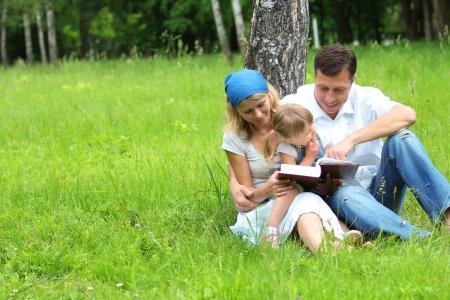 familia cristiana: familia joven con una hija joven lee la Biblia Foto de archivo